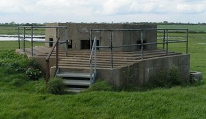 A pillbox on the East coast of England. Part of the defences were built during World War II (the railings are a modern addition)
